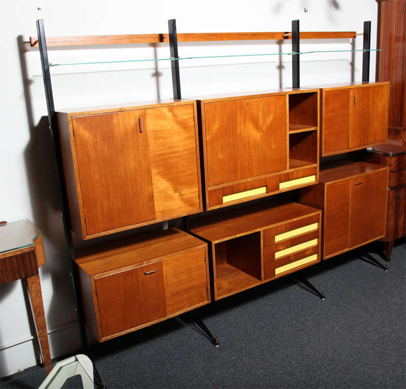 WONDERFUL MODERNIST 3 SECTION BOOKCASE MADE IN MILAN 1960 DESIGNED BY DASSI.WALNUT WITH 4 DRAWERS HAVING A YELLOW BACKGROUND IRON LEGS WITH BRASS ADJUSTABLE FEET AND 3 GLASS SHELVES ON TOP UNUSUAL FORM ,GREAT SIZE.