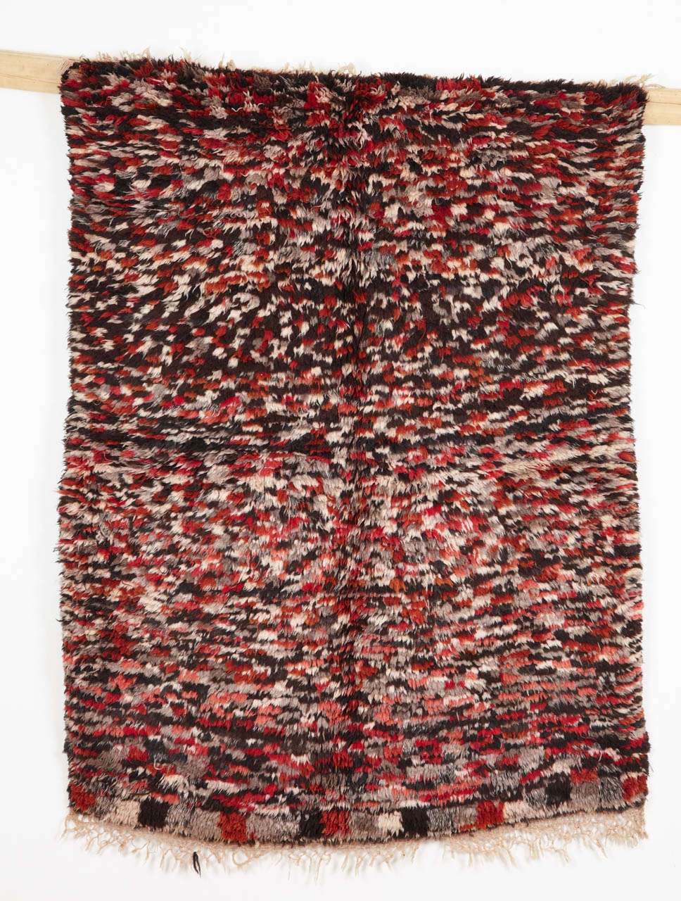 Azilal weavings are often distinguished by a floppy handle and by a relatively thick pile height. This example shows a very dense rendition of the checkerboard pattern, executed in shades of ivory, grey, black and red.