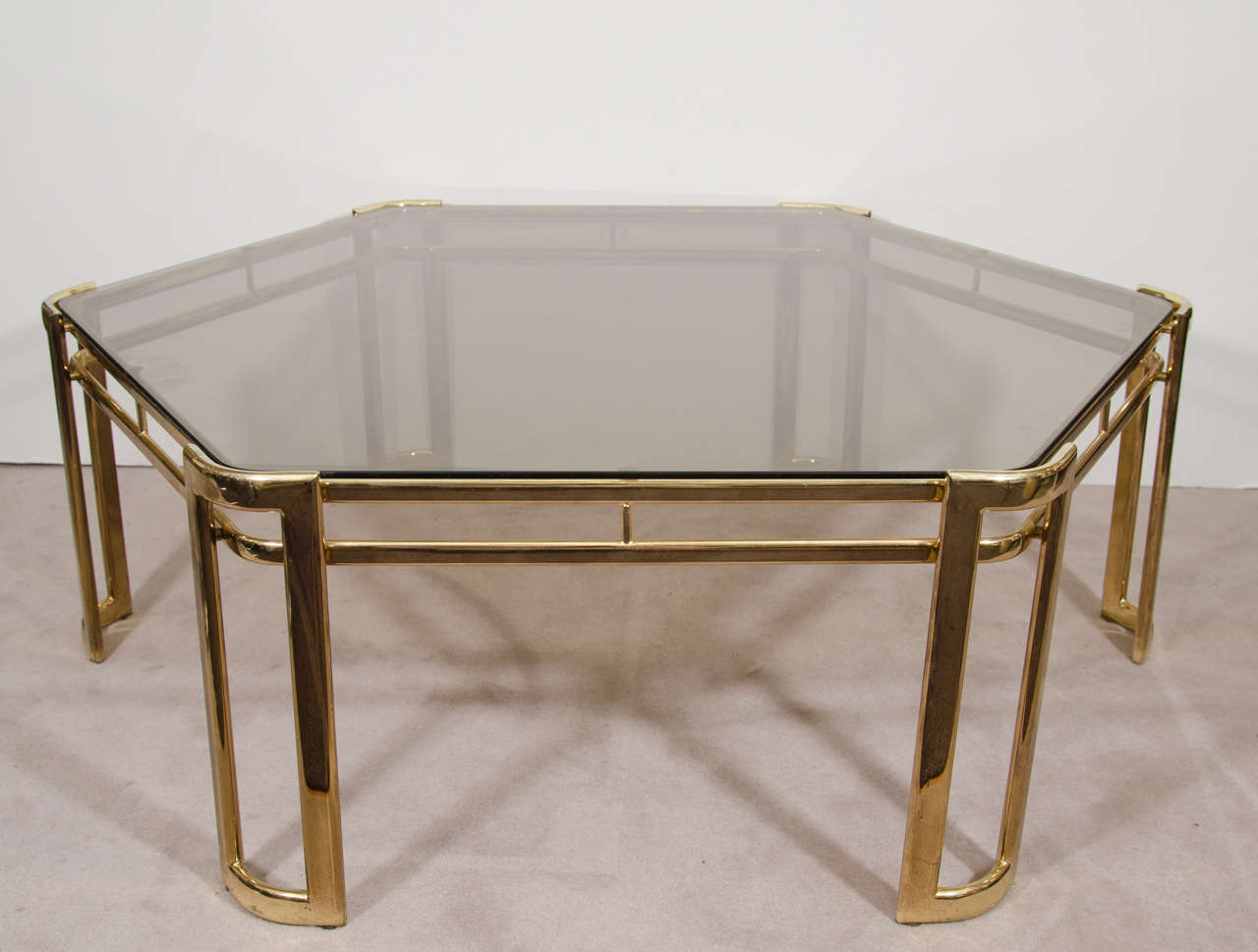 A vintage brass-plated and smoked glass hexagonal coffee or cocktail table.   Good vintage condition with age appropriate wear and patina. One faint scratch to glass.