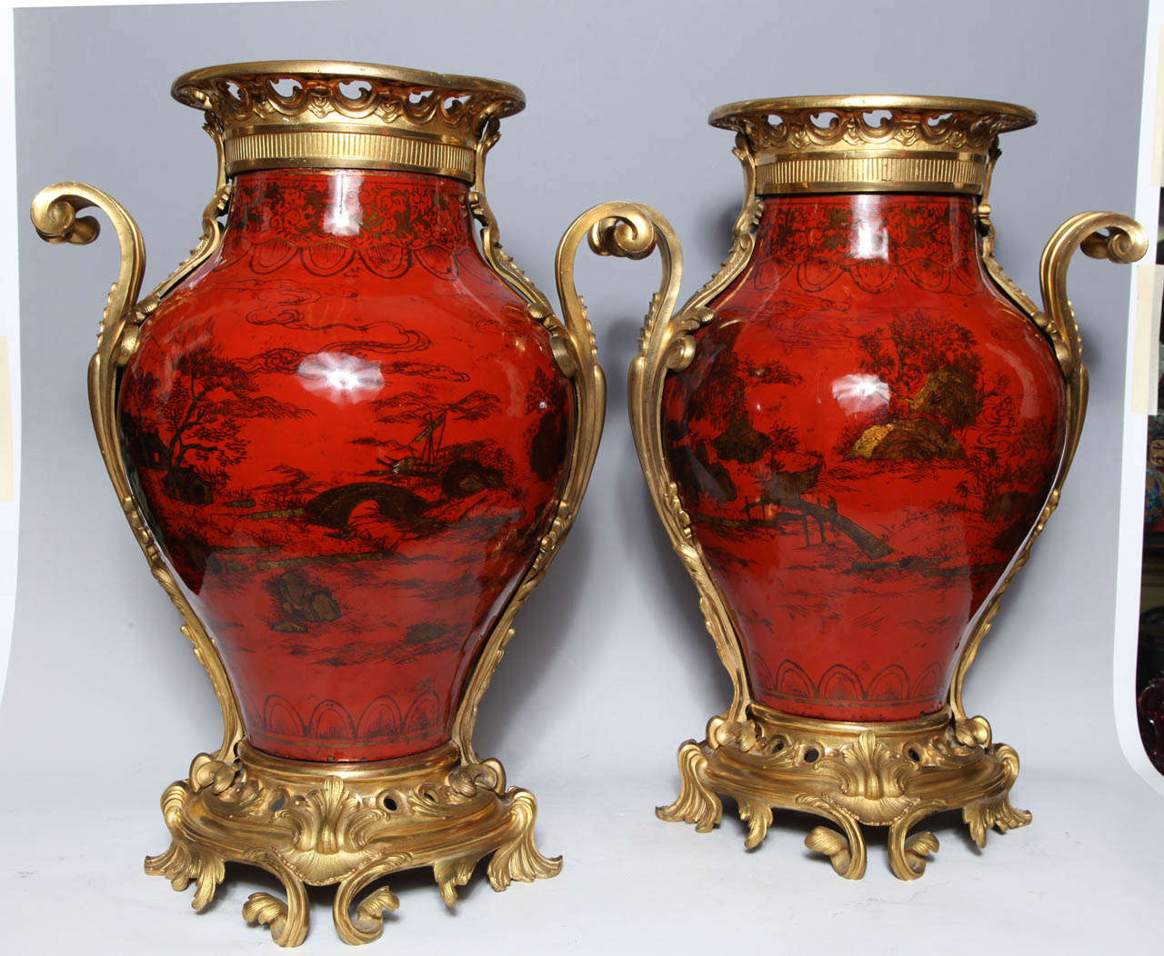 A large pair of antique French transitional period red lacquer, chinoiserie decorated ormolu-mounted vases with gilt bronze Rococo mounts. The vibrant color of these highly polished vases is enhanced by the beautiful scenes of mountains and rivers