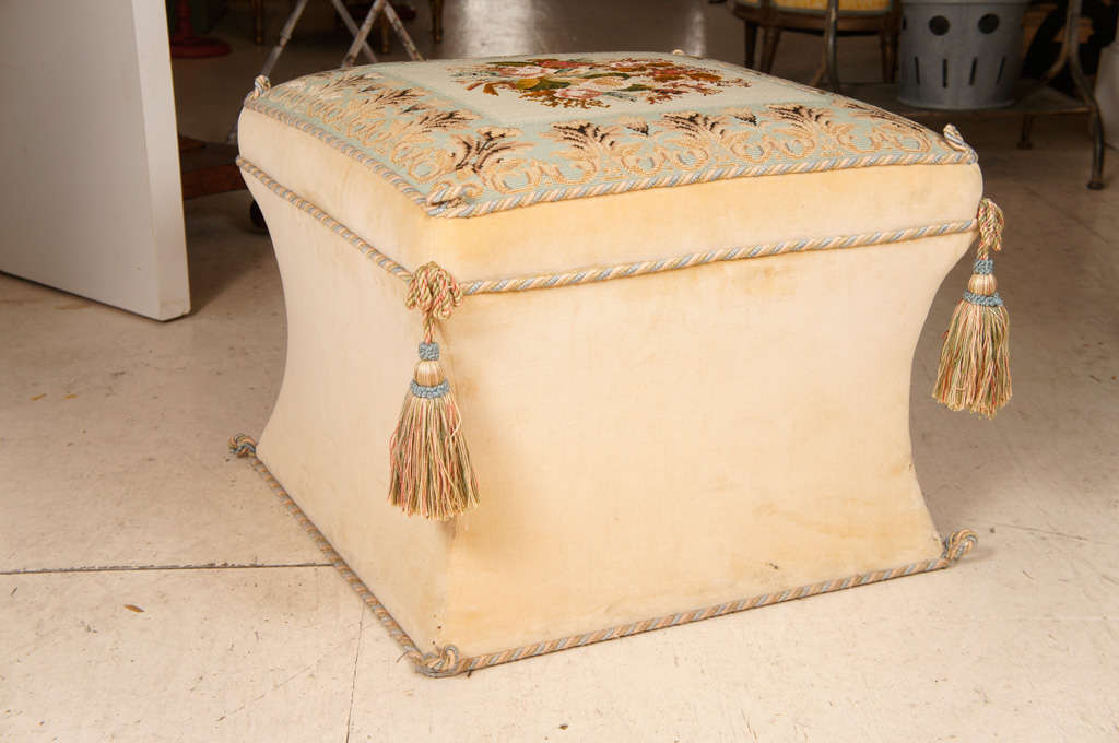 Victorian-style needlework and upholstered ottoman. The square floradl needlework seat with foliate celadon-ground border and tassels at the corners on waisted velvet covered base.
