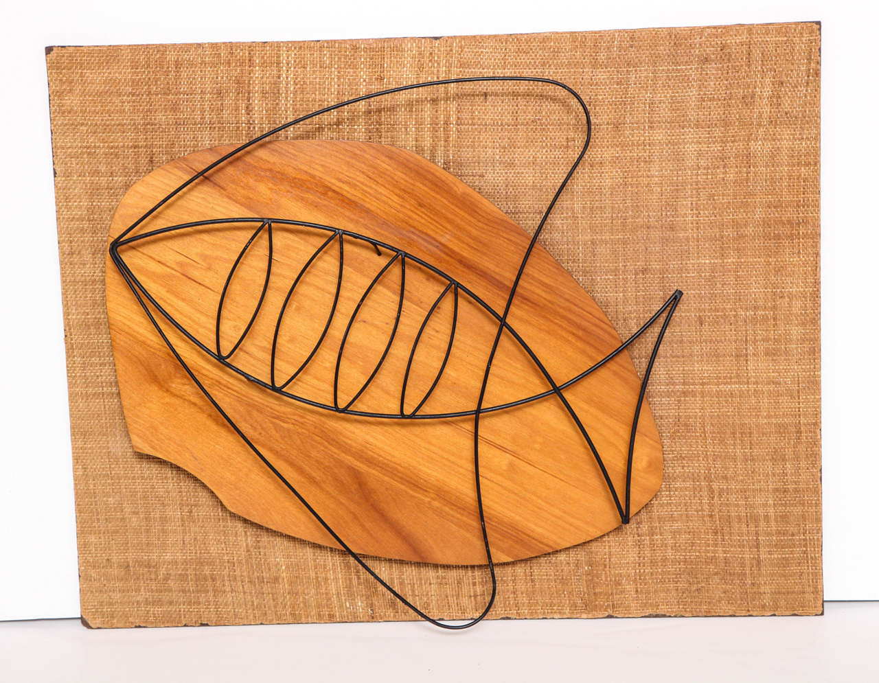 Decorative wall sculpture from circa 1950. Jute fabric backing with a wood and metal sculpture of a fish. The jute fabric has some worn off edges all around.