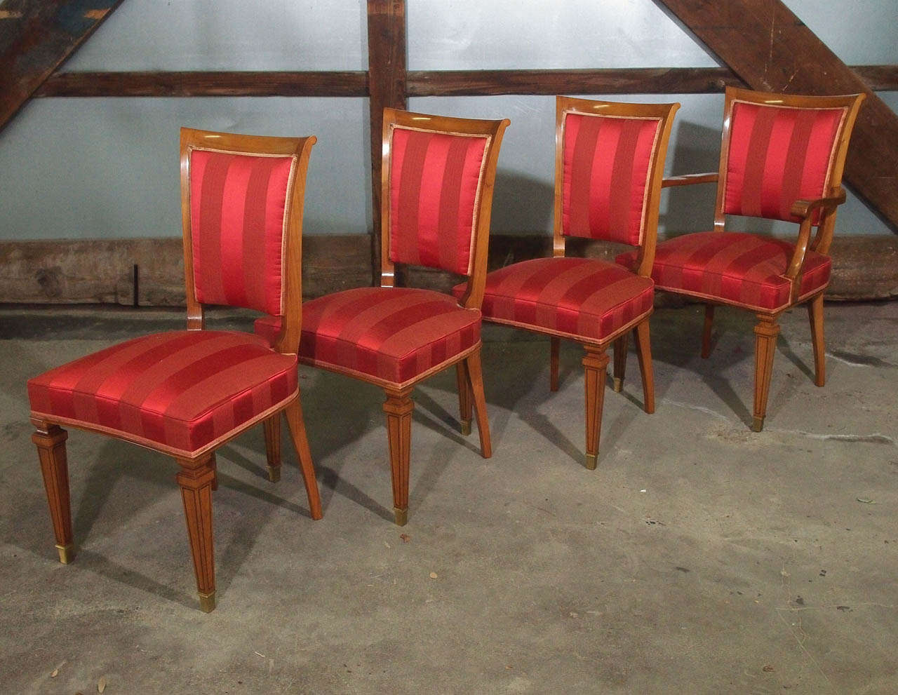 Elegant set of Parisian dining chairs. Made of the finest French walnut and recently professionally French hand polished. Sturdy and solid with solid brass feet and onyx details throughout its legs. Upholstery is original (stripped magenta/red