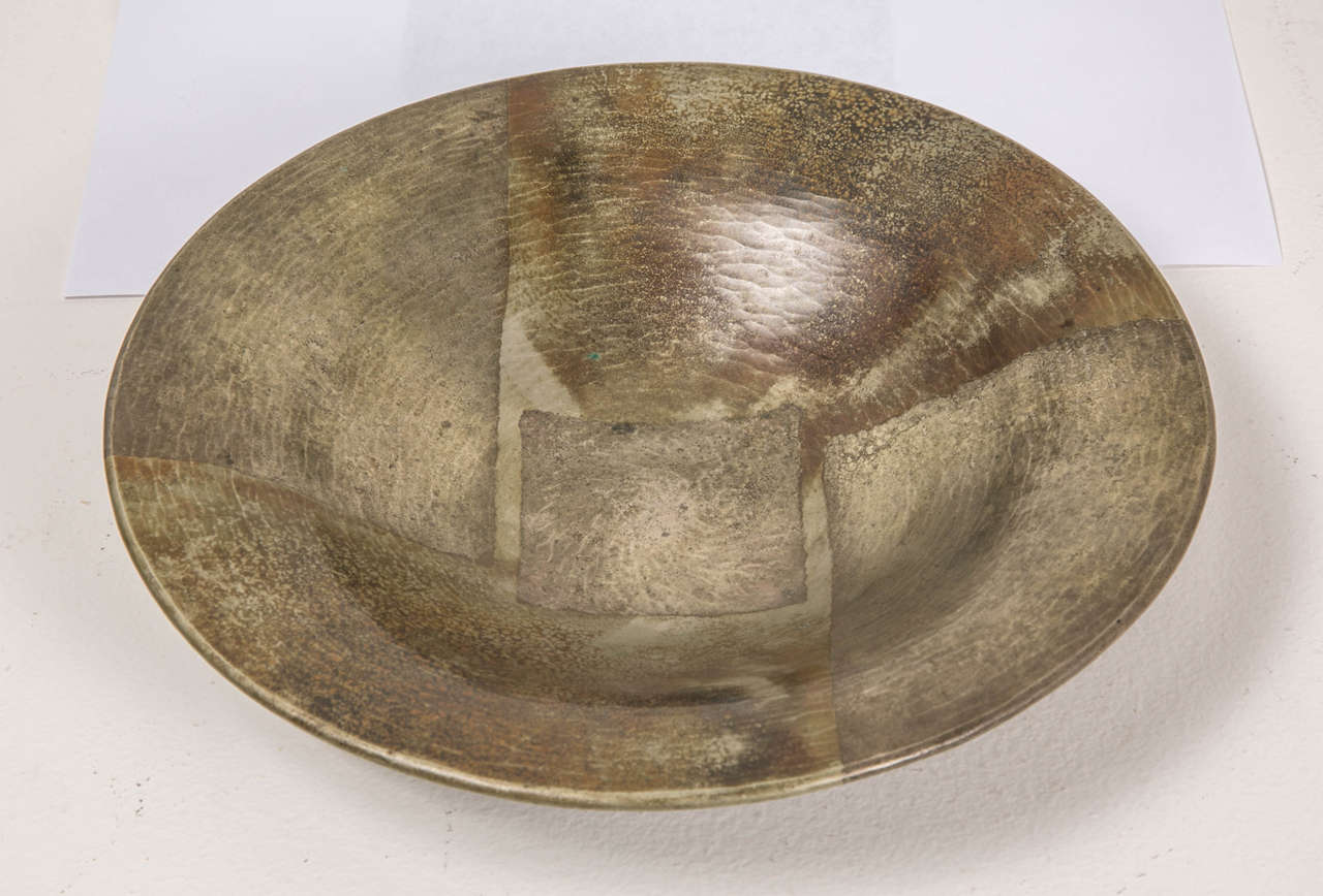 Hammered copperware metal with a sectional geometric decor and a centre square. Silver and oxidized brown patina. Signed Jean Dunand on the back.