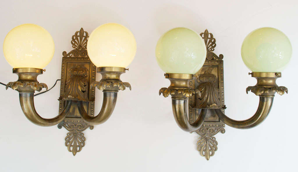 These very elegant bronze sconces have a powerful presence and beautiful design. The original handblown vaseline glass globes make for a very handsome package.