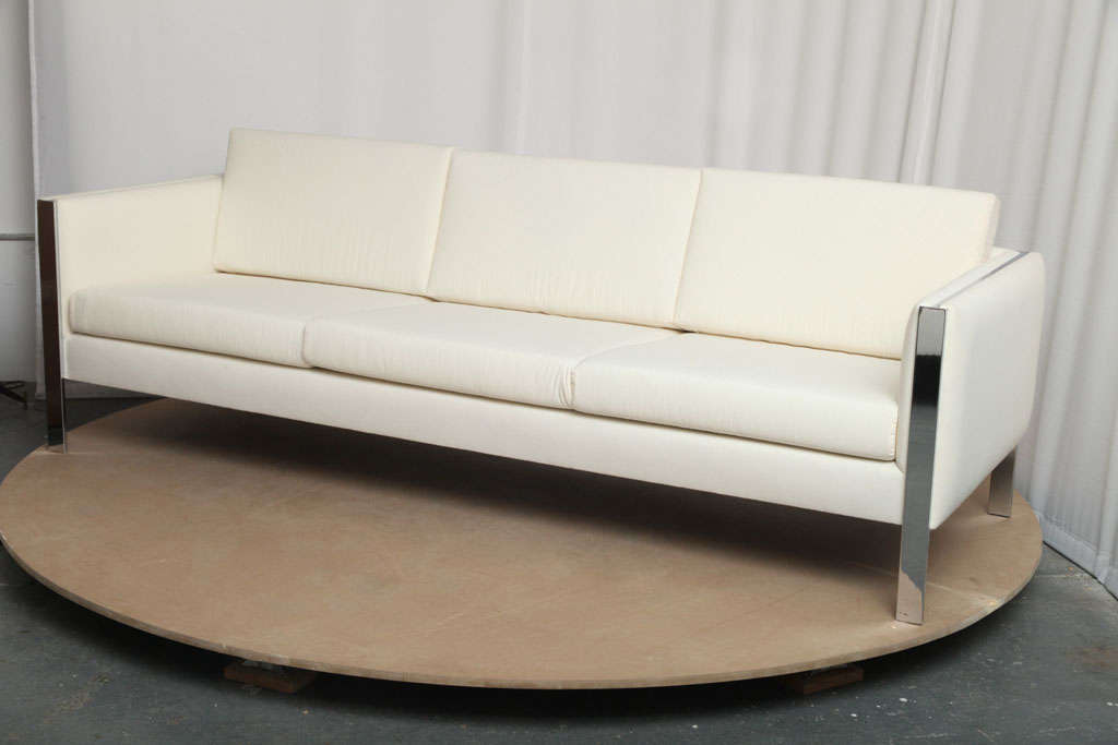 Simple yet really elegant design, the metal structure going though each armrest shows only its narrow side, giving the sofa an illusion of lightness. In the style of Milo Baughman or even Stendig-Massimo-Vignelli.