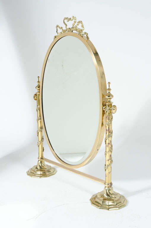 A fantasy tabletop vanity mirror with ribbon crown and garland wrapped posts topped with bishops finials. The oval mirror is set in a brass bezel that tilts and locks into optimum position. Italian, circa 1970.