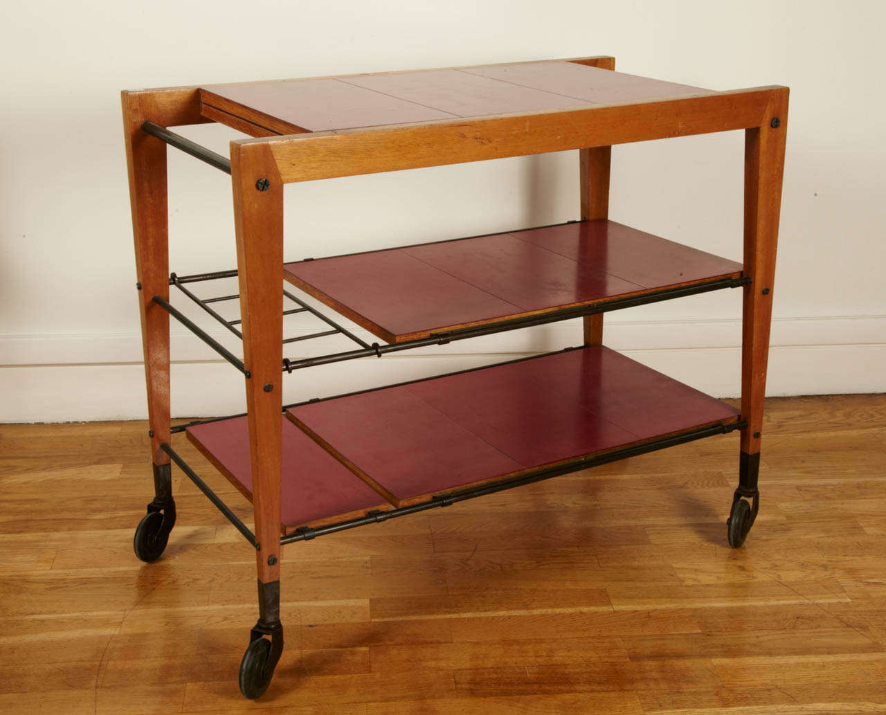 Varnished maple tree trolley table with a black tube steel structure and three sliding paneled boards. The top board unfolds. This table was shown at the 1956 Salon des Artistes Decorateurs and was awarded at the Salon Des Arts Menagers in 1957. The