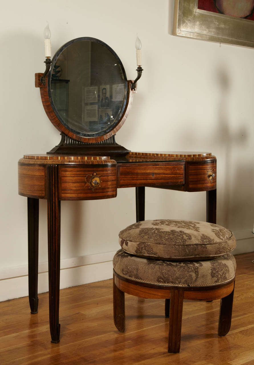 Mahogany dressing table with arrow-tip legs and wound motif feet. Three side drawers, two drawers decorated with floral adornment marquetry (made of mixed woods, metal and ivoirine). Silver plated circular mirror. Two small lighted bronze torcheres.