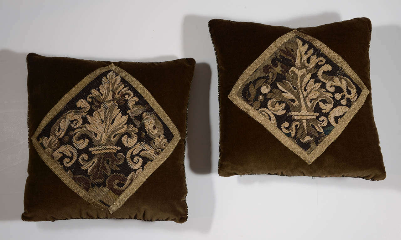 Pair of 18th century tapestry fragment pillows in 100% cotton velvet in rich chocolate hue and finished with gold braid along edge. Tapestries are framed with antique gold ribbon. Down filled.