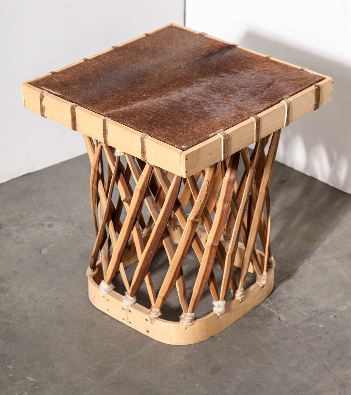 This small wooden table with cowhide top was handcrafted in Mexico. Top is braced underneath with wood. Wood strips along base are secured with leather.