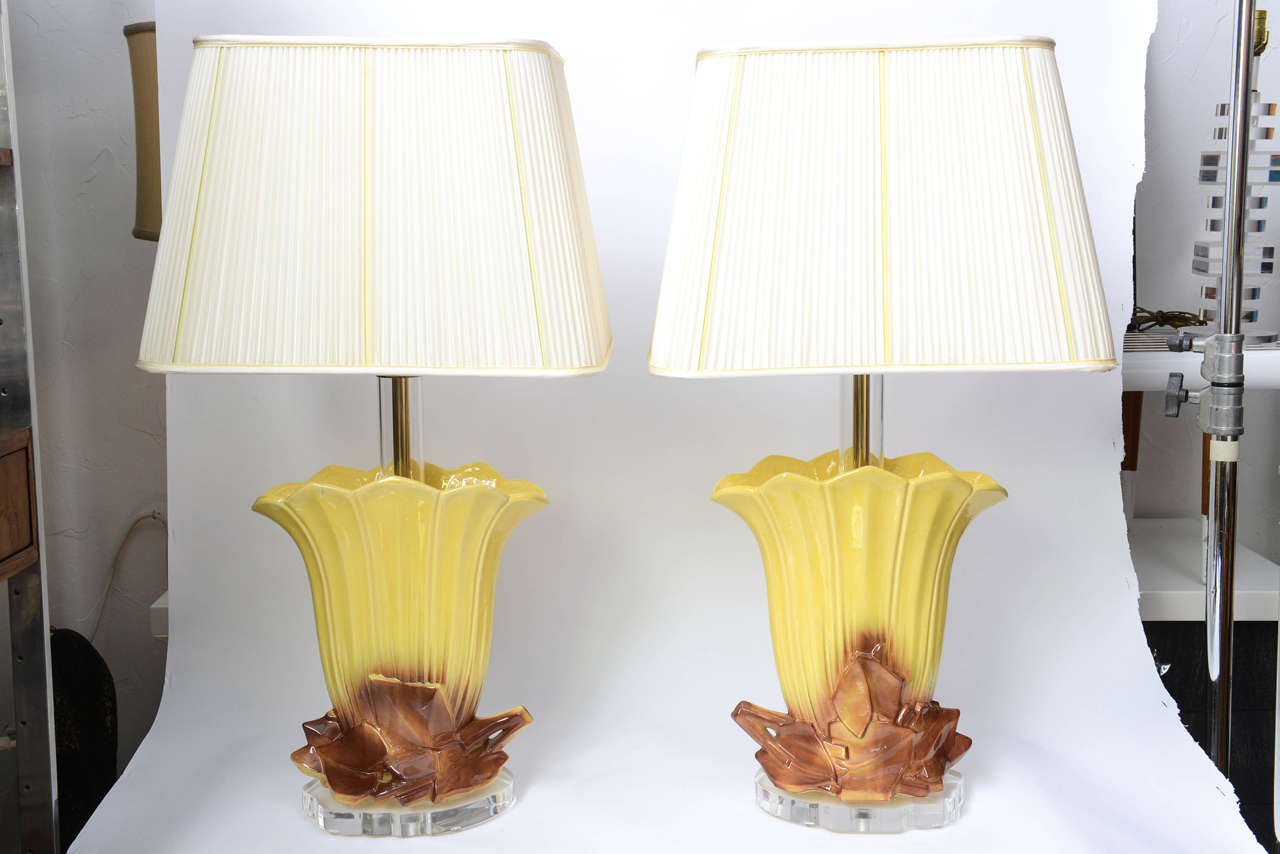 Beautifully retro, these two ceramic table lamps have romantic autumn-leaf groupings at their base which are slightly different on each lamp.  A touch of modernity settles each lamp with a Lucite base.  Original shades included.  Dimensions with