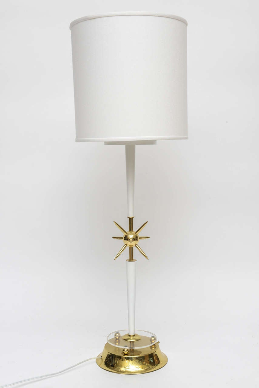 Newly lacquered in a brilliant white hi-gloss, enameled finish, with a tapered neck base. Newly plated and polished brass details. Brass base, atomic symbol center, end caps, neck stem and any brass joinery. Brass round, flared base has three finial