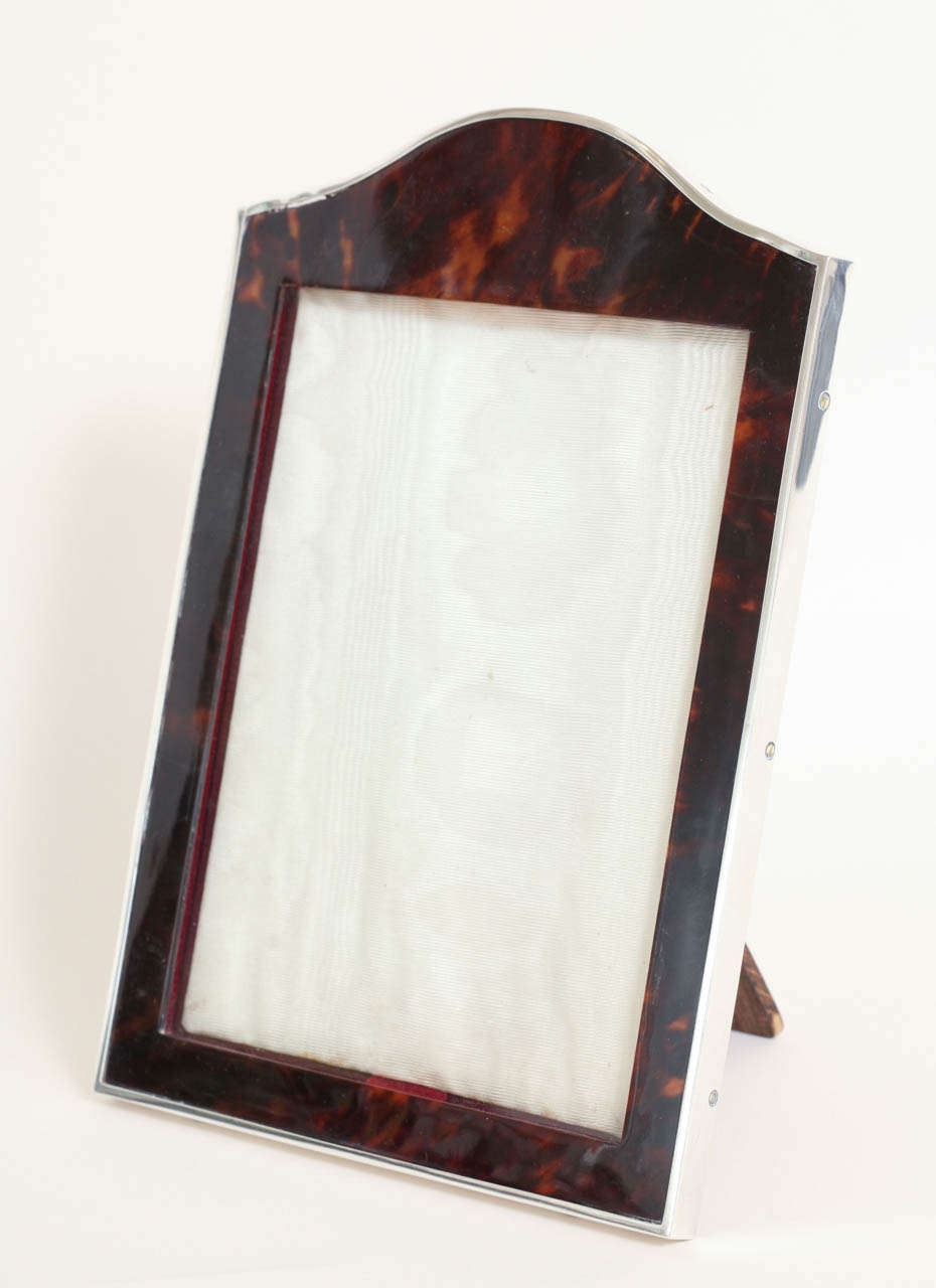Arched faux tortoiseshell frame with sterling silver border. Original leather back and oak stand.