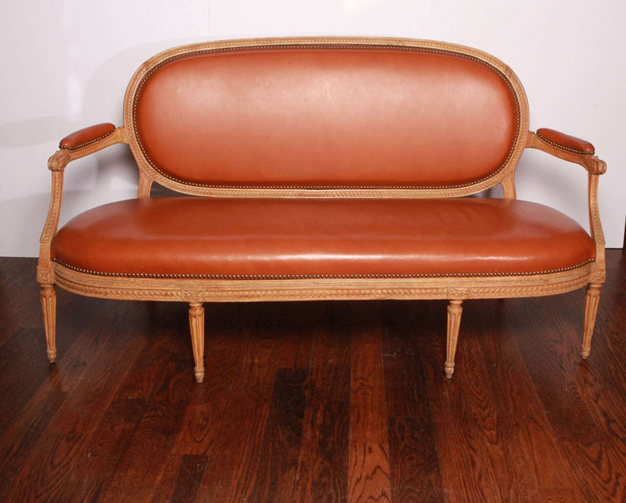 Carved beechwood frame with chestnut leather seat, back and arms. Back and seat are removable. Brass studs. Stamped