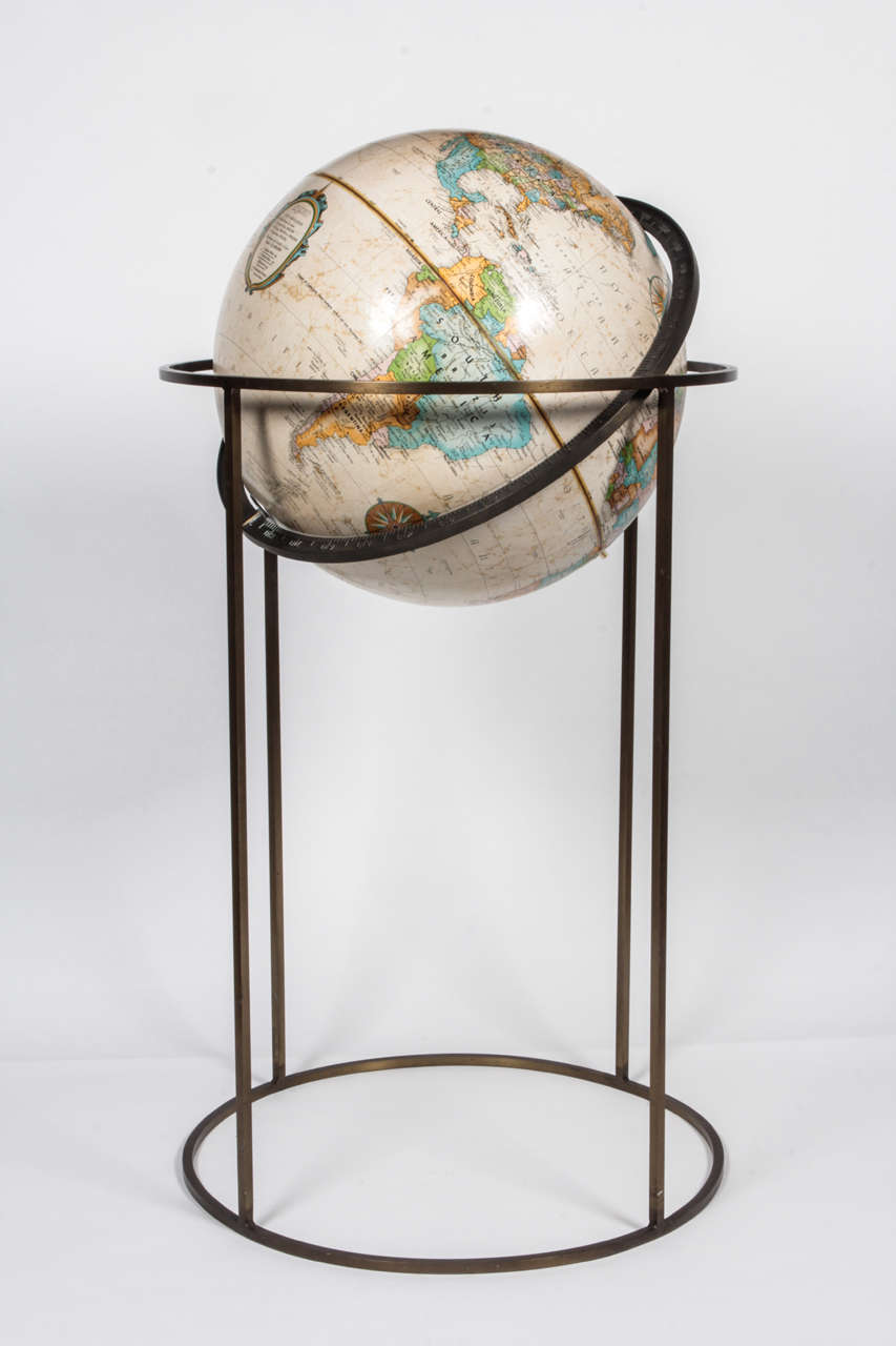 World globe by Replogle in the style of Paul McCobb, USA, circa 1970. Signed.  Beige globe supported by swivel stand in antiqued brass. Featuring square tube design made popular by McCobb.