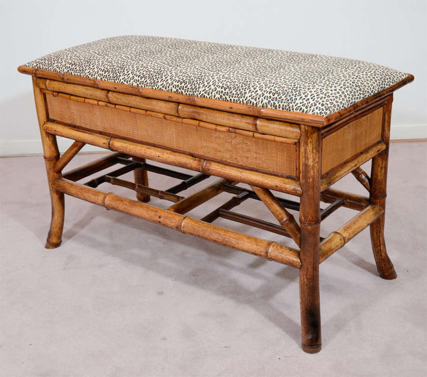 An antique bench with a bamboo frame and recently reupholstered leopard print cushion. The seat lifts up to reveal a storage cabinet.
