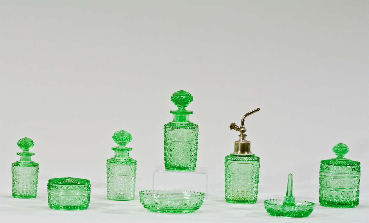 This lovely 8 piece dresser set was made by Val St.Lambert and includes the whole array of pieces for a dresser or vanity mirror. 3 perfume bottles, an atomizer, ring dish, soap dish and 2 covered boxes. It is made in molded crystal, a technique