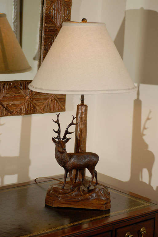 This is a wonderful stag or deer lamp.  The stag is standing in front of the tree which is the neck of the lamp.  The carving is beautiful.<br />