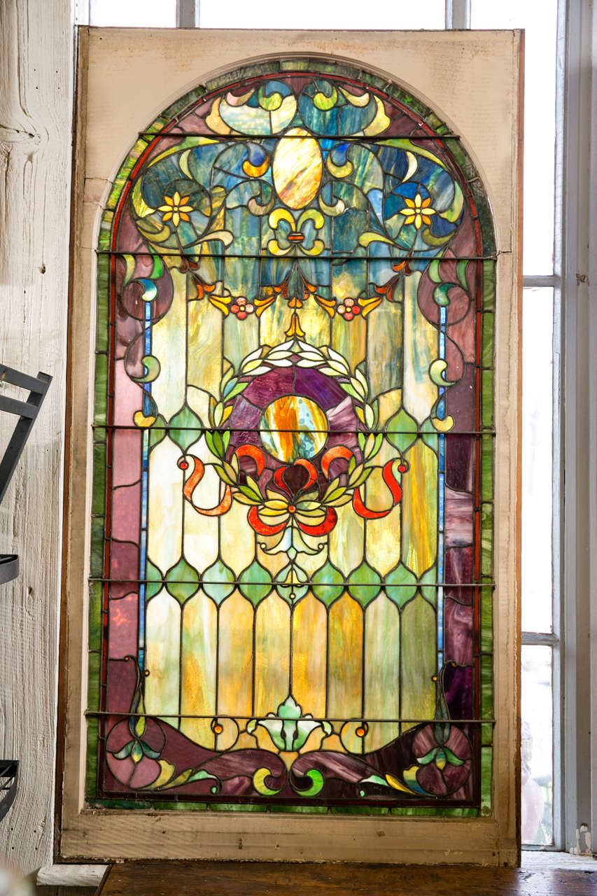 This large antique stained glass window features 13 jewels and an arched top with vibrant color. It has a wreath design in the center. This is one of six matching which were salvaged from the stairwell of the Buena Vista Estate in Greenwich, CT,