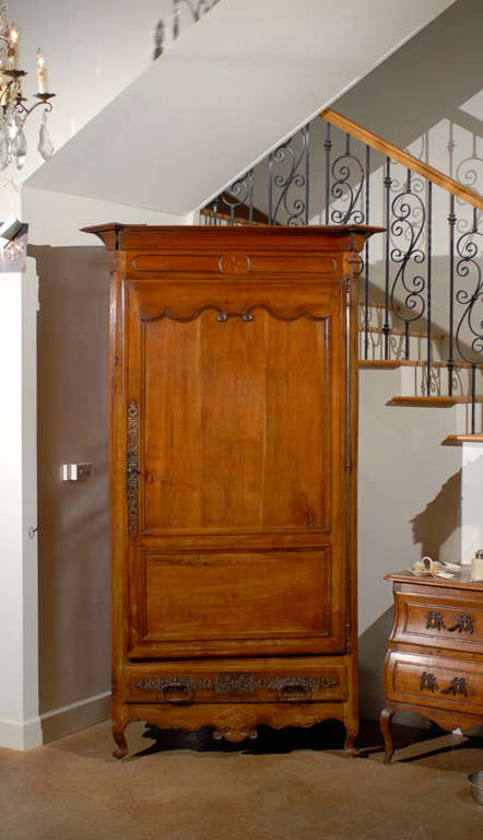 A French early 19th century cherry wood Louis XV style bonnetière from the Charente Region. This French cabinet was born in the Southwestern region of Charente (think Angoulême) , famous for its traditional production of salt and cognac. Originally