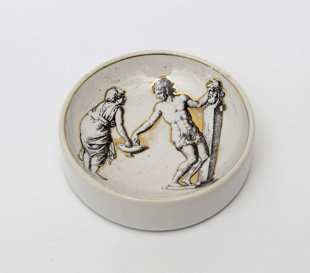 Classical and Roman would elicit the imagery on this signed lovely vintage Piero Fornasetti porcelain gilded bowl/ dish. It is hallmarked on the bottom. It is Mid-Century Modern and classical Italian.
