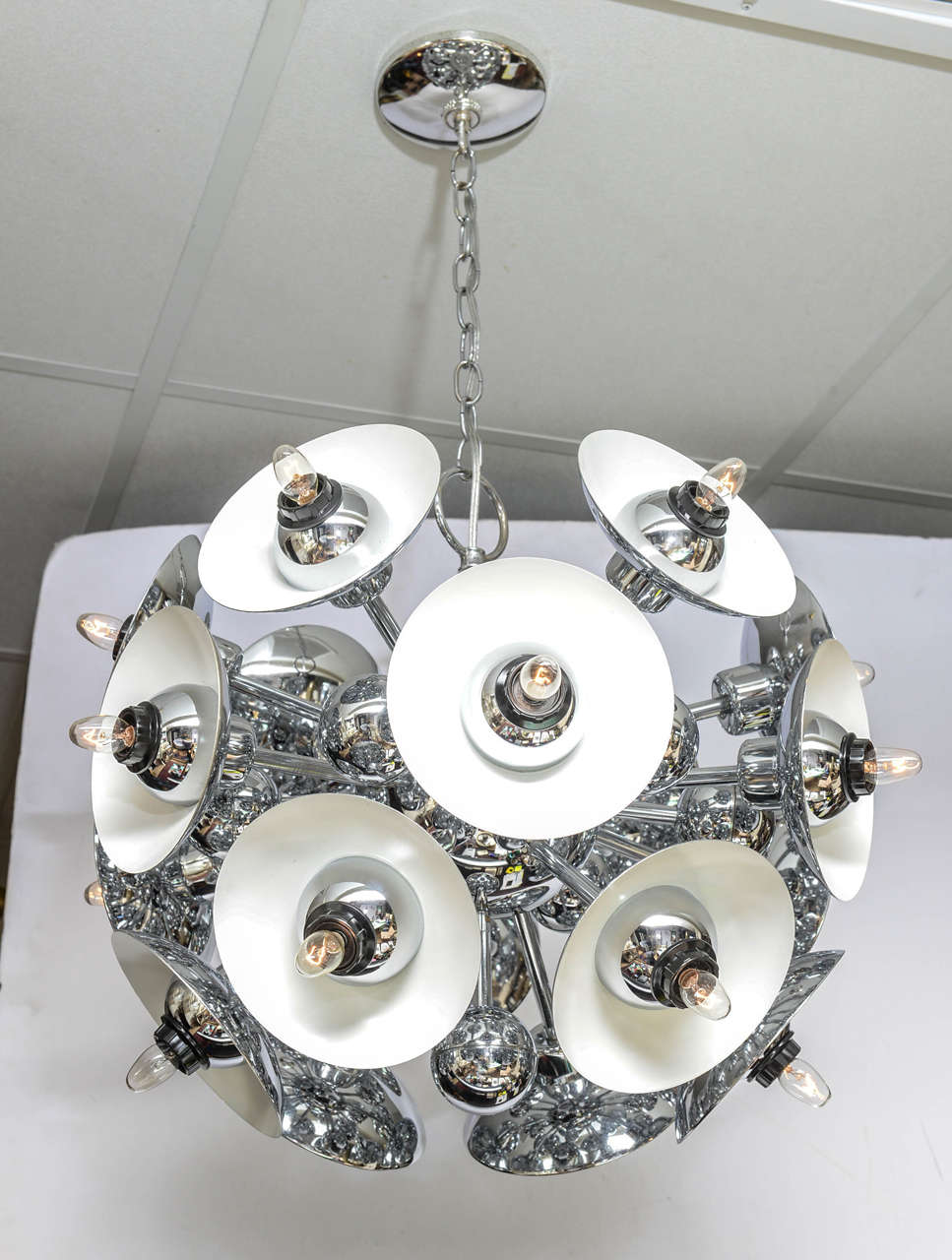 Eighteen chrome saucers on Sputnik arms and spheres throughout. Lots of glam!