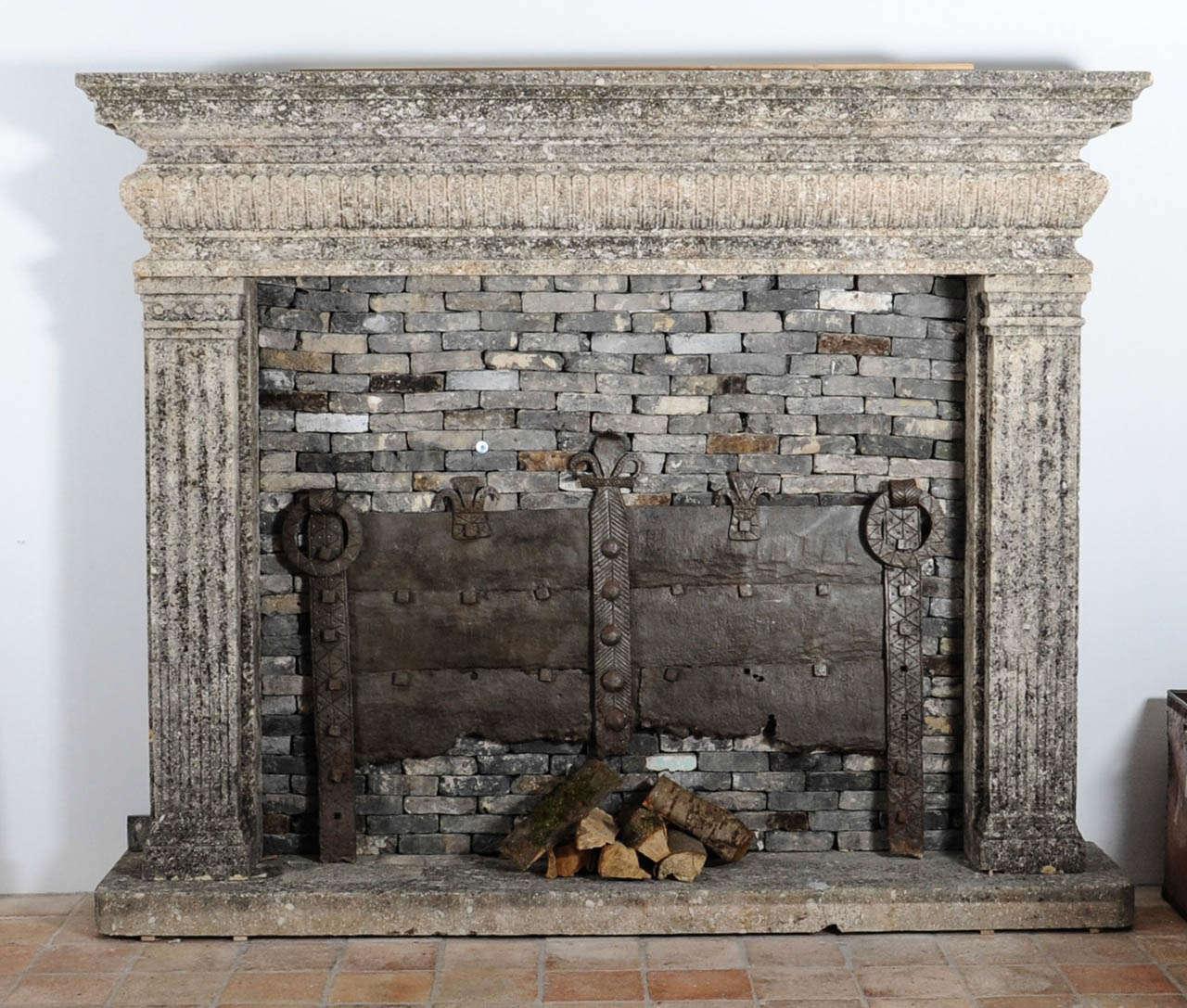 A limestone Italian Renaissance style fireplace and a monumental 16th century French wrought iron fireback 2