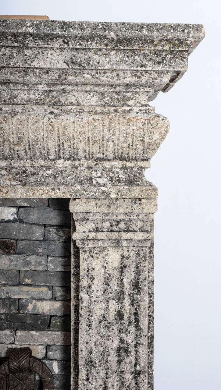 A limestone Italian Renaissance style fireplace and a monumental 16th century French wrought iron fireback 4