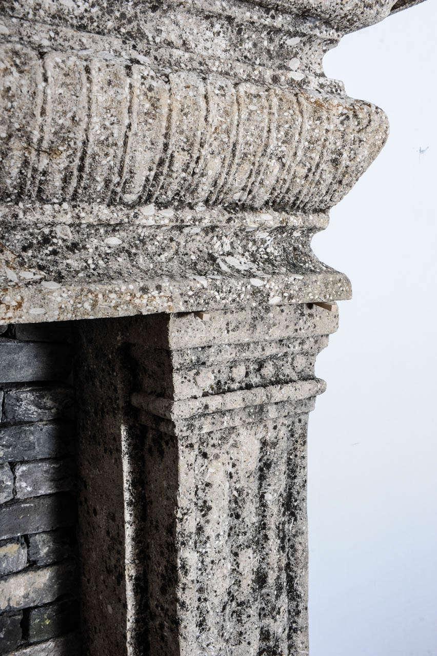 A limestone Italian Renaissance style fireplace and a monumental 16th century French wrought iron fireback 8