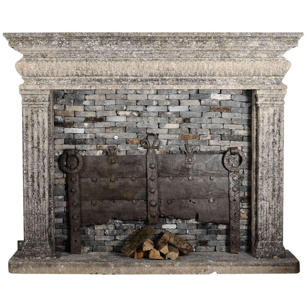 A limestone Italian Renaissance style fireplace and a monumental 16th century French wrought iron fireback 1