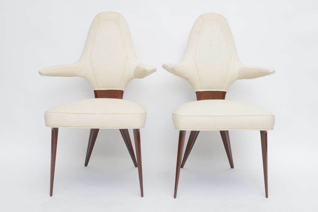 The upholstered back with channel seat over an x framework with splayed tapering legs can be sold as pairs.