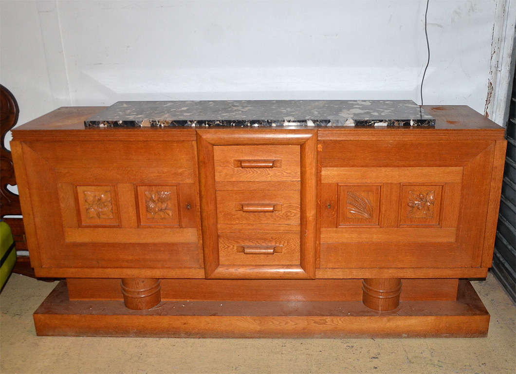 Large oak sideboard with carved door panels of ears of wheat, hazelnut branches and other fruits and flowers. Drawer handles carved winding. Beautiful quality of wood and workmanship.