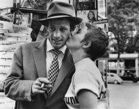 Jean-Paul Belmondo and Jean Seberg kiss in front of a kiosk