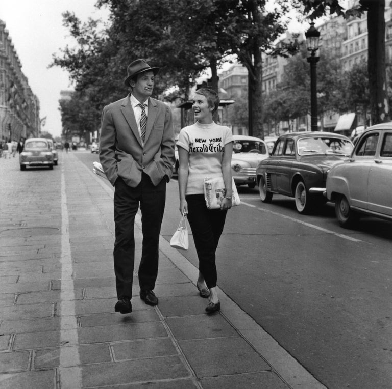 Raymond Cauchetier Black and White Photograph - Jean-Paul Belmondo and Jean Seberg off-set on the Champs Elysees