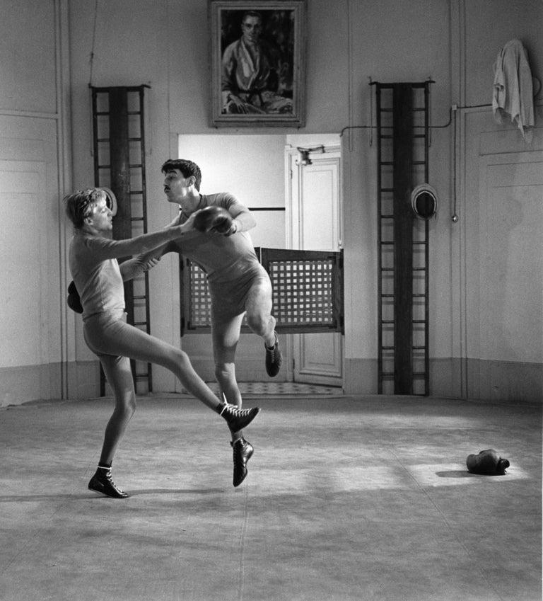 Oskar Werner and Henri Serre mimic a 1900 waltz in a boxing ring, Paris - Photograph by Raymond Cauchetier