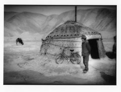 Kyrgyz herdsman watches his camels from outside his yurt, LandscChinese Turkesta