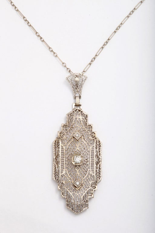 It sits quietly at the neck calling attention to its dignity. Spun of platinum and white gold, in linear and vertical form, the pendant is delicate, strong and like urban 1920's architecture, it epitomizes Art Deco design. The eye is drawn first to