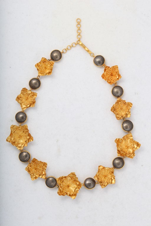 A flower necklace composed of nine 18kt yellow gold flowers interspersed with sterling silver beads that have been bezel set with 18kt yellow gold. The necklace can be wrapped around the wrist twice and worn as a bracelet. Length: 15 inches Width: