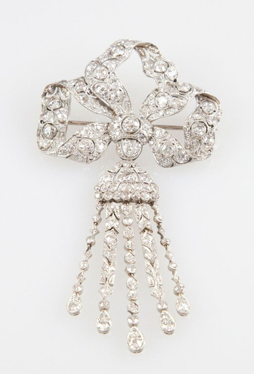 The undulating bow brooch is bead and bezel-set with old European-cut, old mine-cut, single-cut and rose-cut diamonds and suspends a 5 chain tassel of diamonds. All settings have millegrain edging. Total diamond weight is approximately 8.75 carats,