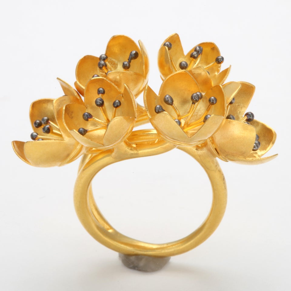 An 18kt yellow gold buttercup ring composed of six buttercup buds. Each buttercup is set with clusters of 18kt yellow gold stamen and rhodium plated sterling silver beads. Size 6.25 Width: 1.50 inches Flower Height: .50 inch
