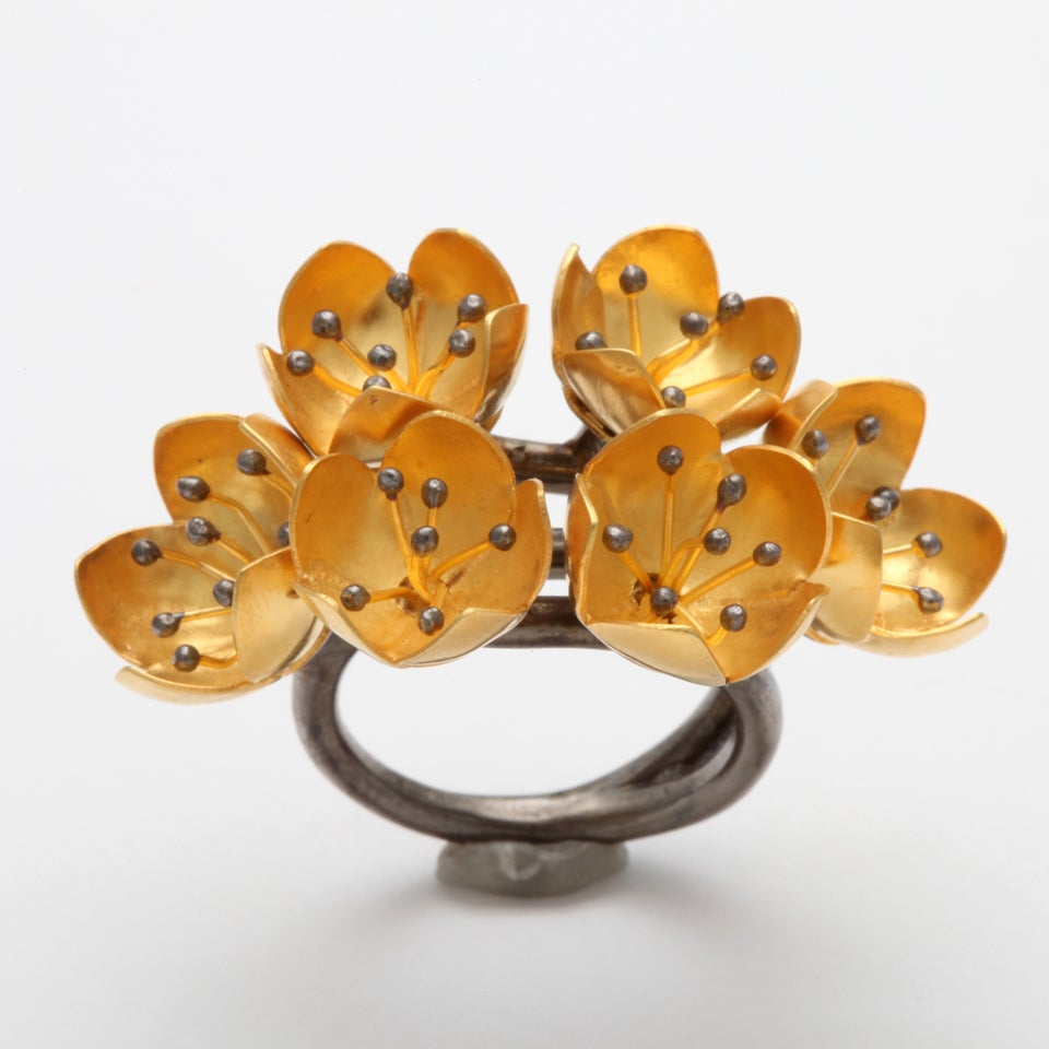 An 18kt yellow gold and rhodium plated sterling silver buttercup ring. the ring is composed of six buttercup buds and each buttercup is set with clusters of 18kt yellow gold stamen and rhodium plated sterling silver beads. The ring shank is made of