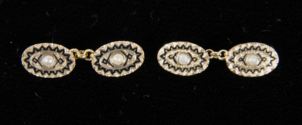 These 14k yellow gold cufflinks feature a pearl set in the center with an Art Deco black enamel geometric design.