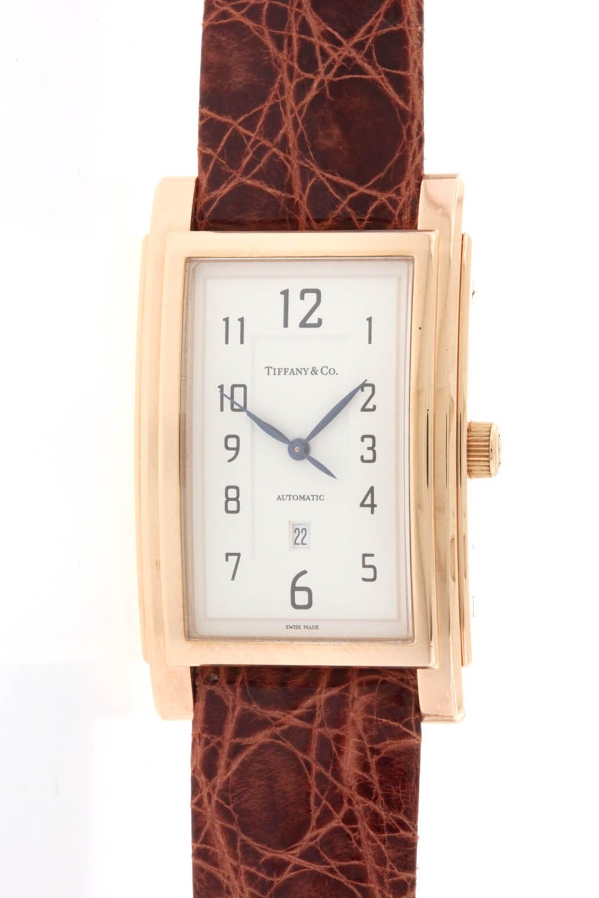 18k rose gold Tiffany & Co 'Grand' automatic rectangular wristwatch with center seconds and date. Elegant case measuring 30mm x 49mm, with triple stepped bezel, white dial with painted Arabic numerals, blued steel hands, date aperture at 6 o'clock,