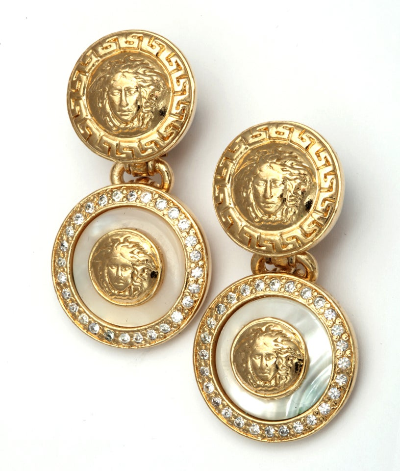 Gianni Versace white and gold dangling earrings with iconic Medusa motifs.