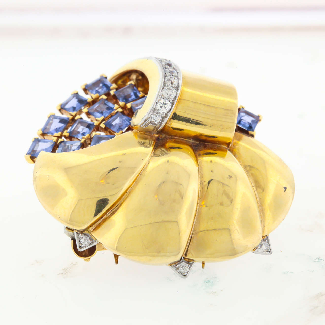 Circa 1940's 'Reflection'  pin in 14K gold, sapphire and diamonds, signed Trabert Hoeffer Mauboussin, the famed American jeweler from 1929 through 1953. The very Retro-style scalloped brooch, 1-7/8