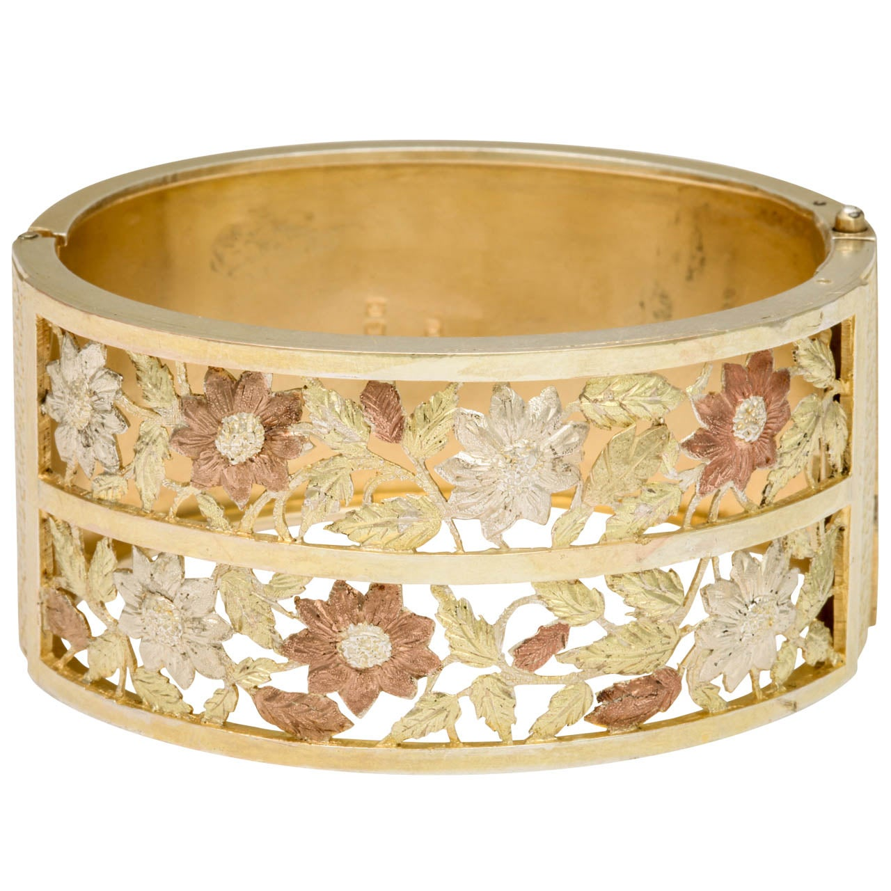 Golden hues fill this bracelet with the intensity of midday sun. Two rows of flowers, with realistic engraving, have been cut from the silver and play among the vines. Crosshatched engraving borders the bracelet sides. The bracelet is English c.