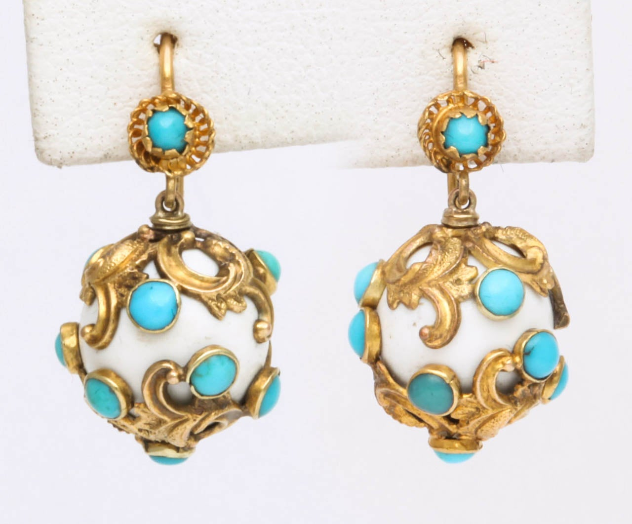 Fun and easily wearable, this pair of Victorian earrings is made with dangling orbs of white enamel wrapped in golden vines. The vines terminate in turquoise floral buds. At the earlobe is a  small flower also centered by a turquoise. Light in color