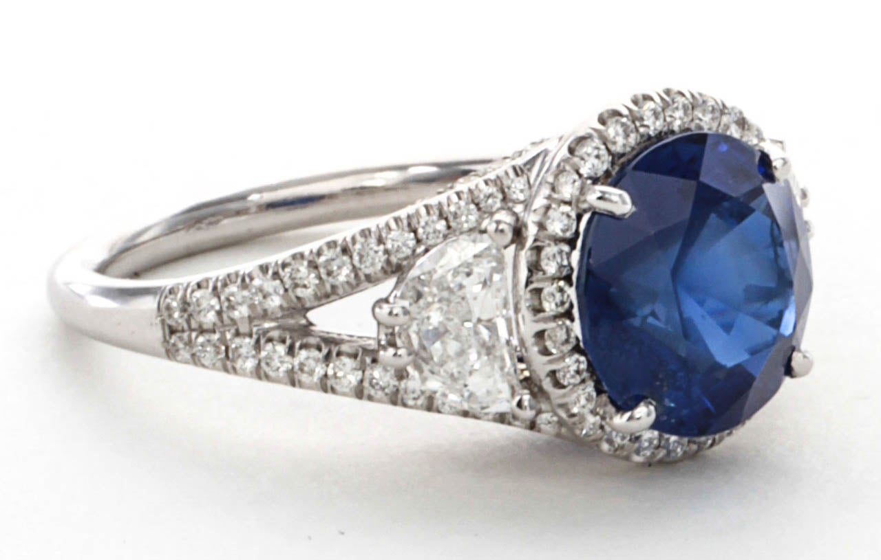 3.45 carat round cut center sapphire. The sapphire is certified natural no heat with exquisite cornflower blue color. This important sapphire is set in a custom diamond mounting featuring half moon cut side diamonds and micro pave detail set in 18k