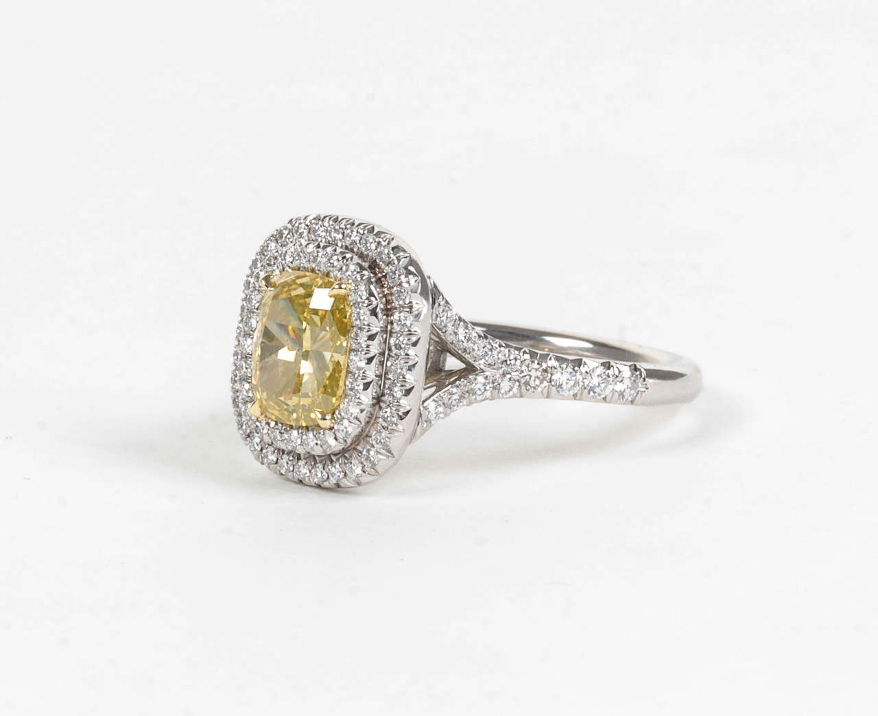 1.54 carat GIA Certified vivid yellow VS2 cushion cut center diamond.  The center diamond is set in a handmade platinum and diamond mounting featuring 0.80 carats of round brilliant cut white diamonds.  A beautiful engagement or cocktail ring to